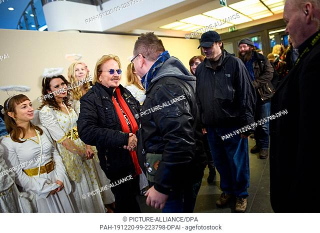 20 December 2019, Berlin: Musician Frank Zander (M) welcomes the guests with a handshake at his 25th Christmas celebration for the homeless and needy at the...