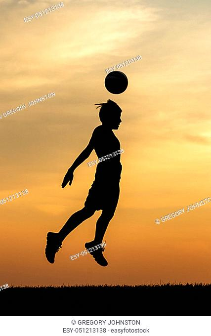 A young athlete heads a soccer ball at sunset in this concept photo