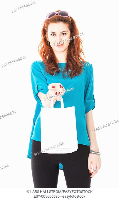 Studio portrait of attractive young woman with shopping bags and sunglasses