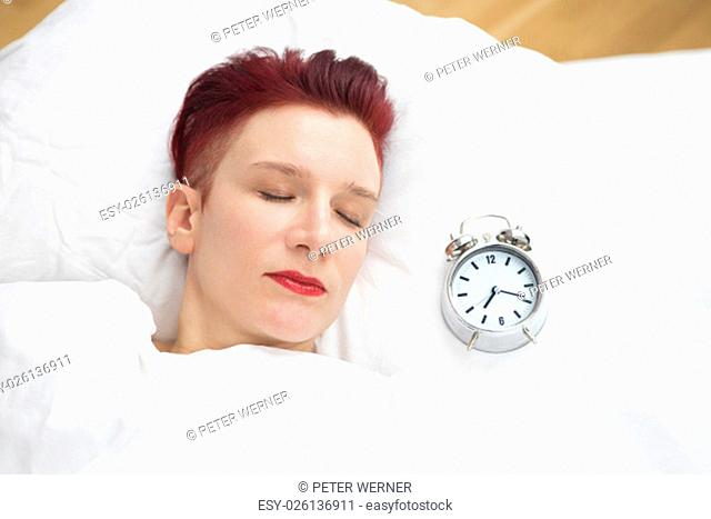red-haired woman sleeping in bed with alarm clock next to her