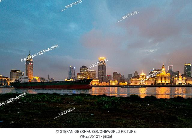 China, Shanghai, The Bund skyline at sunset with a freighter in the foreground