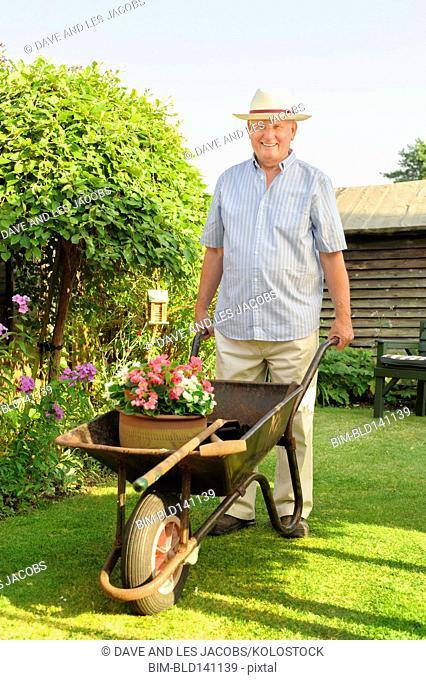 Caucasian man pushing wheelbarrow in backyard