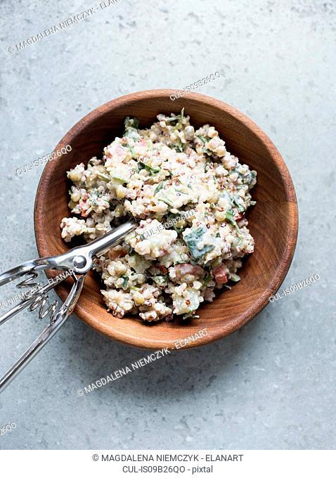 Bulgur salad in wooden bowl with scoop