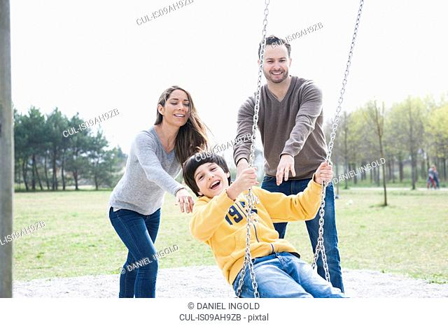 Parents pushing son on park swing