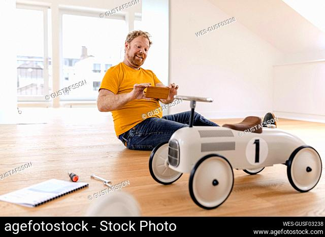 Happy man taking cell phone picture of toy car