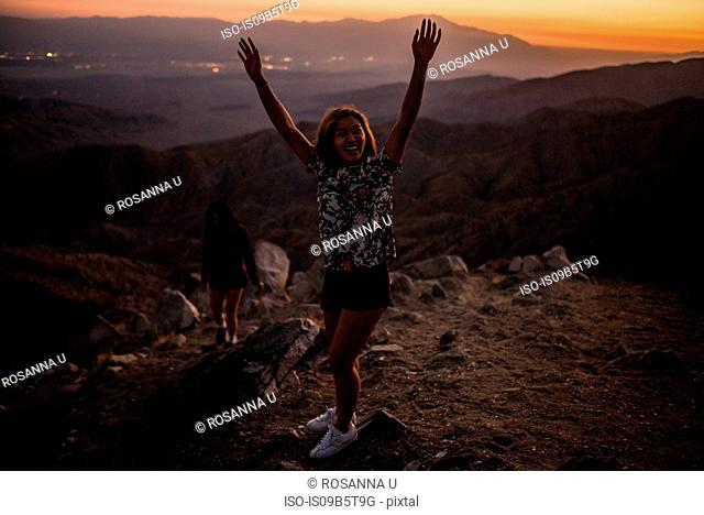 Portrait of young woman with hands raised in Joshua Tree National Park at sunset, California, USA