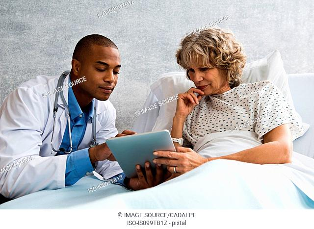 Doctor showing digital tablet to patient in hospital