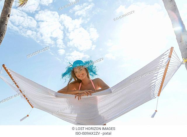 Portrait of young woman lying on hammock at Miami beach, Florida, USA