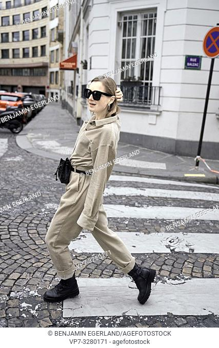 fashionable woman walking at street at zebra crossing during fashion week, in Paris, France