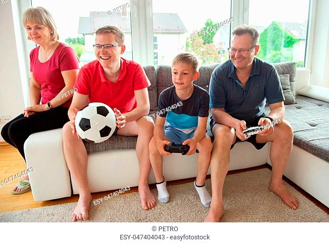 Grandparents, their son and grandson are playing computer game emotionally at home on sofa