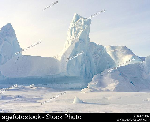 Iceberg frozen into the sea ice of the Melville Bay, part of the Baffin Bay, near Kullorsuaq in the far north of West Greenland