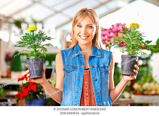 Lächelnde junge Frau hält zwei gelbe Blumen (Tagetes) in Gärtnerei