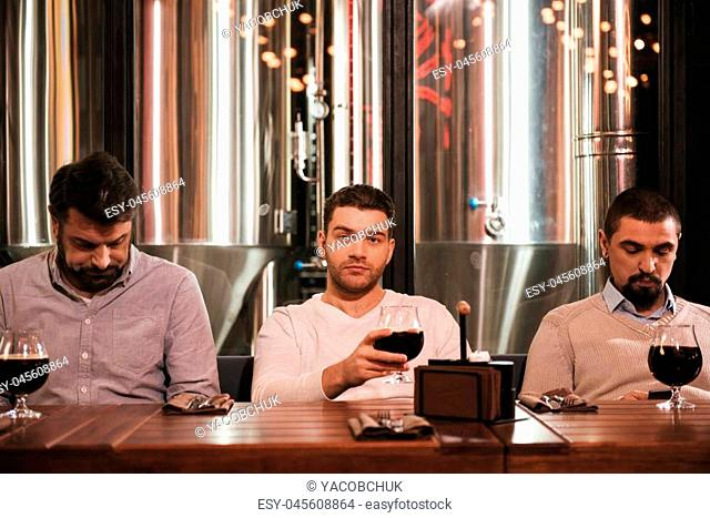 Age of technology. Serious handsome nice man sitting between his friends and drinking beer while looking at you
