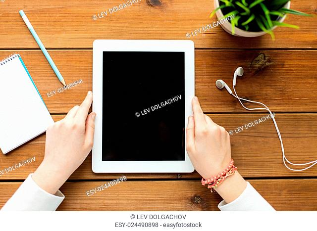 business, education, technology, people and advertisement concept - close up of woman with blank tablet pc computer screen on wooden table