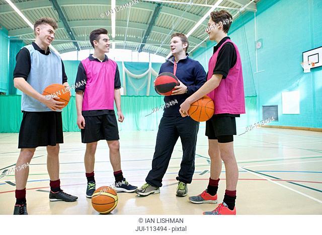 Gym teacher teaching high school students basketball in gym