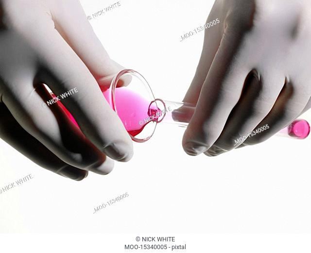 Person wearing rubber gloves pouring pink liquid into vial close up studio shot