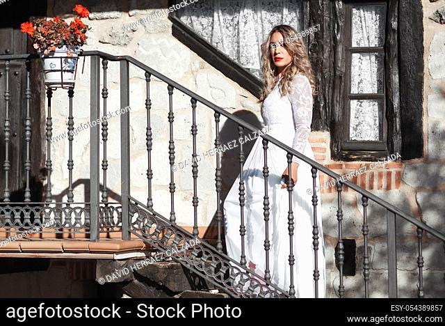 Sensual woman on staircase. Woman bride in white wedding dress. Girl with glamour look. Fashion model