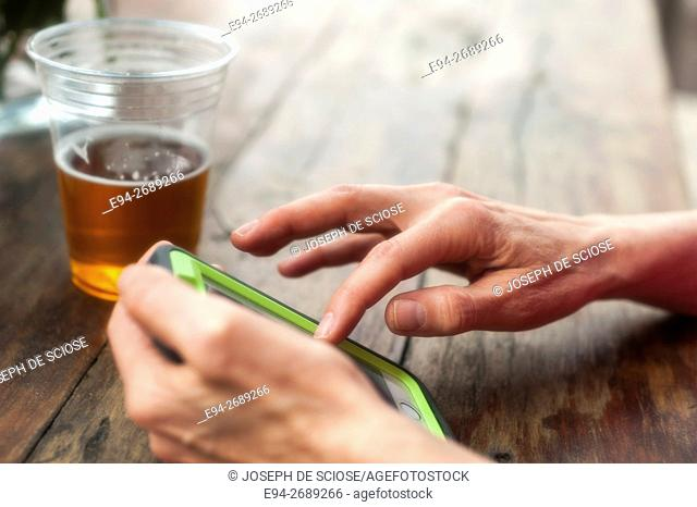 Close up of a woman's hand on a mobile phone with a cup of beer on the table in the background