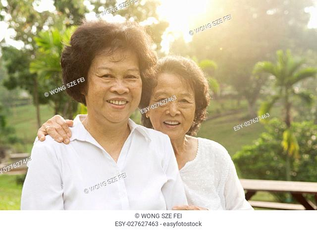 Portrait of healthy Asian seniors mother and daughter sitting at outdoor nature park, morning beautiful sunlight background