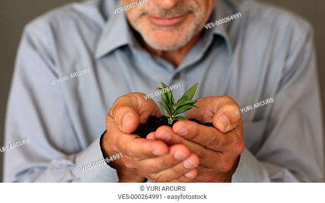 A senior man holding a little plant in his hands and smiling