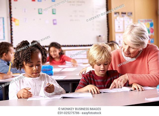 Senior teacher helping elementary school pupil in class
