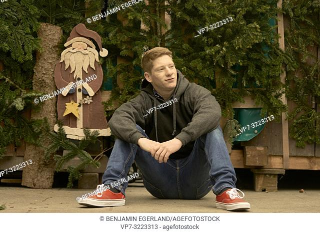 young man sitting on the floor, evergreens, christmas, Santa