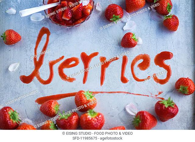 The word 'berries' written out in strawberry sauce
