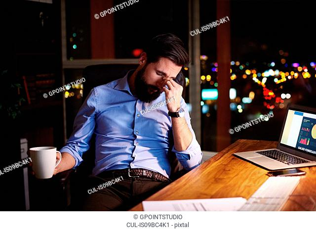 Tired young businessman at office desk at night