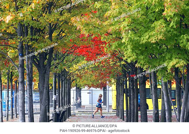 26 September 2019, Berlin: At temperatures around 20 degrees Celsius, a jogger walks through a park in front of the Federal Chancellery past autumn-coloured...