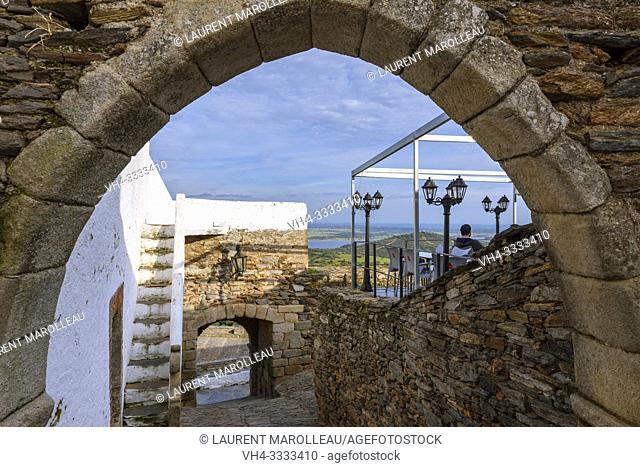 Archway in Traversa da Cisterna and Cafe terrace with Alqueva Lake in the background, Monsaraz, Reguengos de Monsaraz Municipality, Evora District