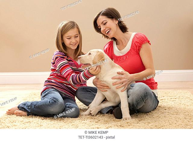 Mother and daughter 10-11 playing with Labrador on carpet