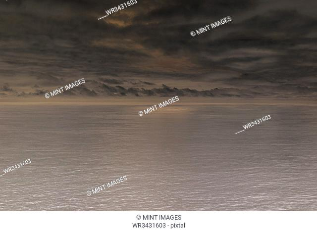 Inverted image of dark and moody clouds over a calm ocean surface at dusk