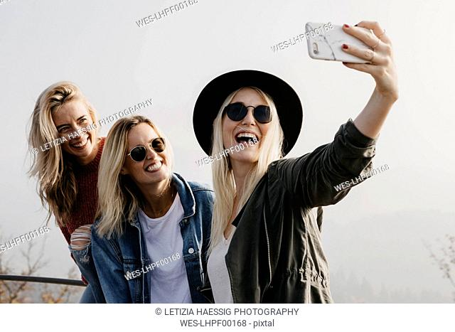 Three happy young women taking a selfie outdoors