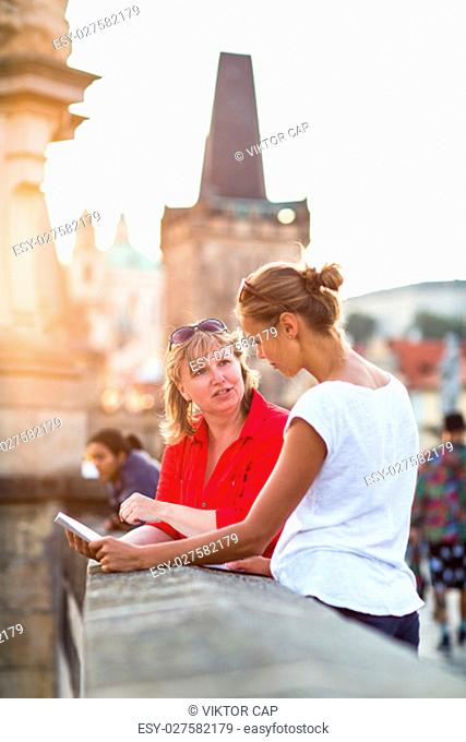 Mother and daughter traveling - two female tourists studying a map, discovering a new city