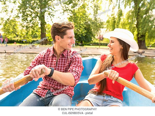Young couple rowing a boat together in Regents Park, London, UK