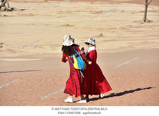 Asian tourists in long, sun-protective clothes, in Dead Vlei, taken on 01.03.2019. The Dead Vlei is a dry, surrounded by tall dune clay pan with numerous dead...