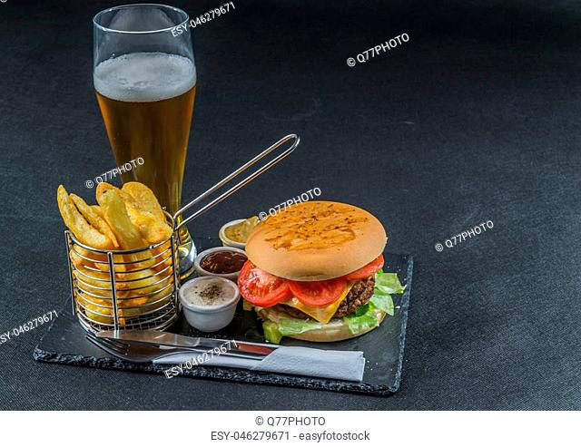 right side view on a flame grilled double stack cheeseburger, lettuce, tomato, with three sauces, chips in a metal basket, beer, tasty set