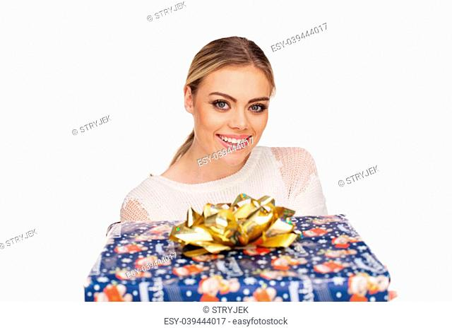 Young woman holds a gift wrapped in christmas paper, isolated on white