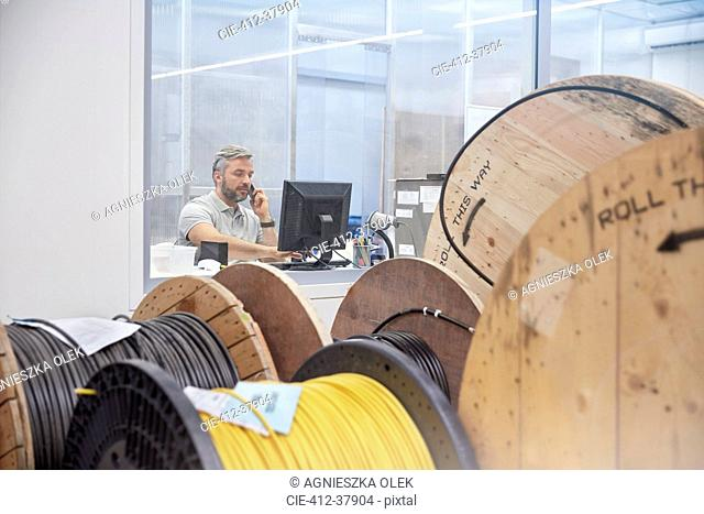 Male supervisor working at computer and talking on ell phone behind spools in fiber optics factory