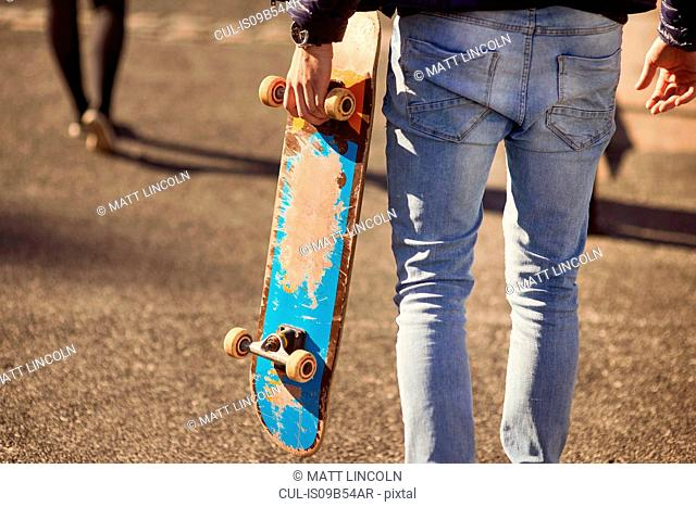 Young man walking outdoors, carrying skateboard, rear view, low section, Bristol, UK