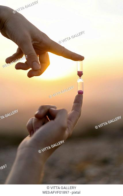 Close-up of man's hands holding an hourglass at sunset