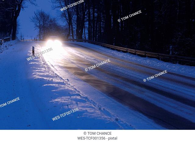 Germany, Bavaria, Schaeftlarn, car on country road in winter
