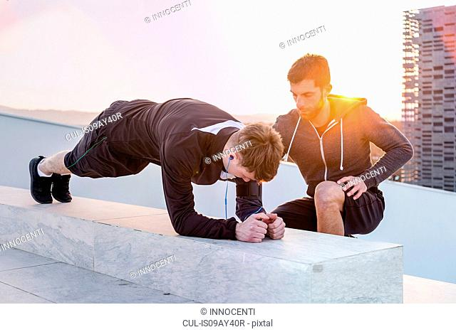 Mid adult man helping young man exercise
