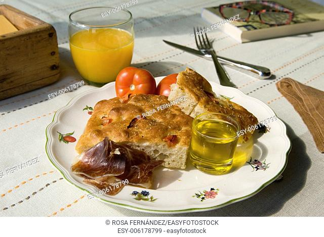 Breakfast with focaccia, olive oil, jamon iberico, orange juice, tomato and book with glasses over a sunny table, Madrid