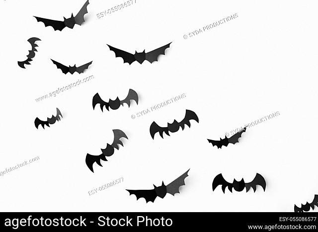 flock of black paper bats over white background