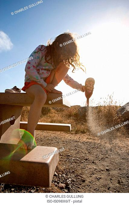 Girl emptying sand from shoe