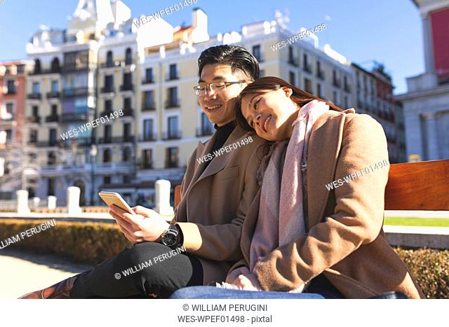 Spain, Madrid, young couple resting on a bench and using cell phone in the city