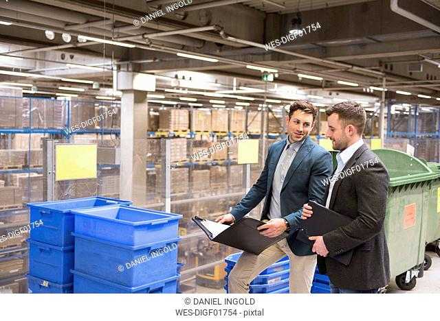 Two businessmen with documents talking in factory warehouse