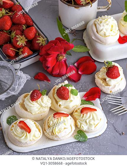 baked meringue with cream and fresh strawberries, behind the tray with red berries, top view