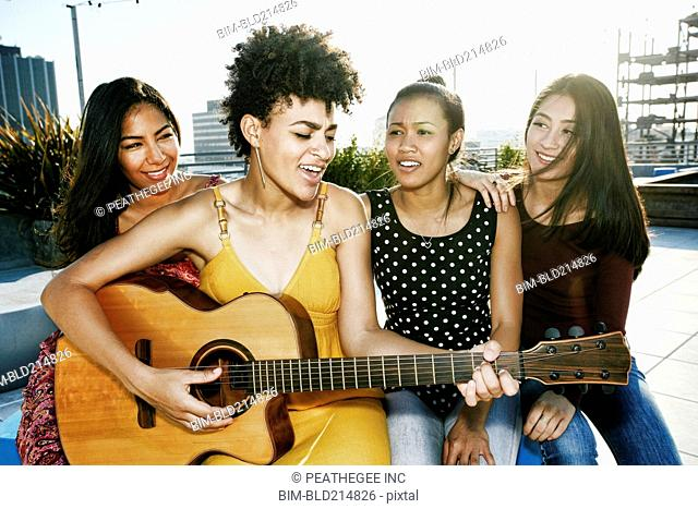 Women playing music and singing on urban rooftop